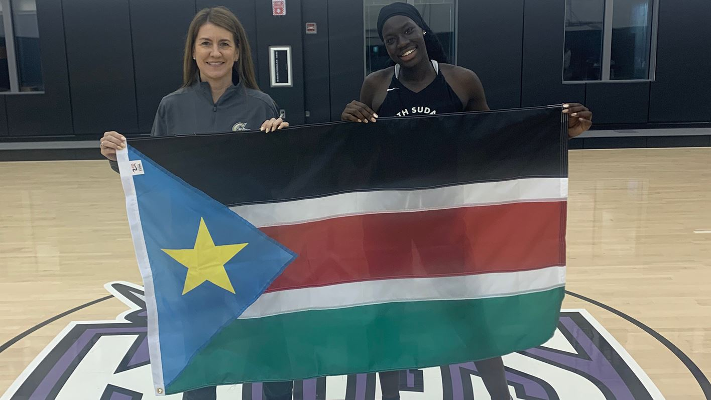 Nya Lok and Coach McCombs hold the South Sudanese flag at the team's training camp